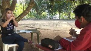 Joyce Barcelos Barbosa traduz as lições em libras para que o jovem possa seguir o cronograma de ensino. Na comunidade onde ele mora, o acesso à internet é quase inexistente