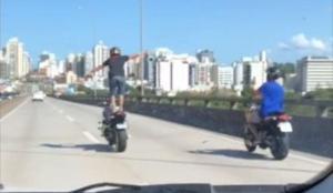 O homem fica em pé sobre o banco, com as mãos fora do guidão, e depois empina a moto, enquanto uma pessoa, também de moto, filma ao lado