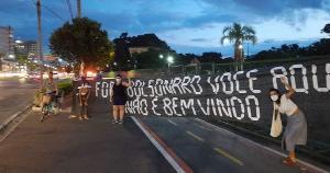 Opositores do governo expuseram faixas contra a crise sanitária, política e econômica do país. Presidente ficou cerca de sete horas no Estado e inaugurou casas populares