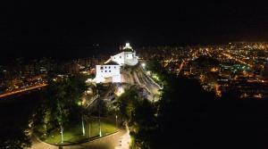 Do alto do morro, o principal cartão-postal do Espírito Santo tem a sua imponência e arquitetura histórica realçadas pelas luzes de LED