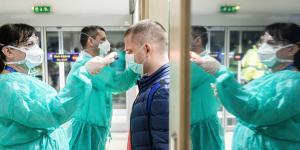 Why Coronavirus Spread Across the Globe: Mobile Population and Mild Symptoms